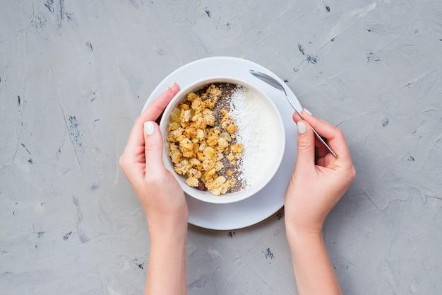 Ciotola di granola casalingo con yogurt e semi di chia su fondo di pietra dalla vista superiore Foto Premium