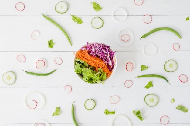 Ciotola di insalata spalmata con la rapa; cetriolo; fette di cipolla con fagiolini sulla scrivania in legno Foto Gratuite