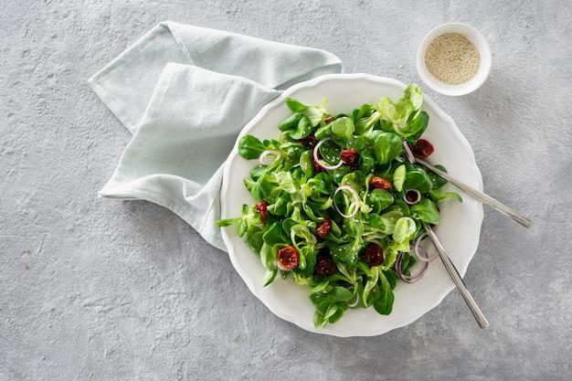 Ciotola di insalata verde con foglie di mache e pomodori al forno Foto Premium