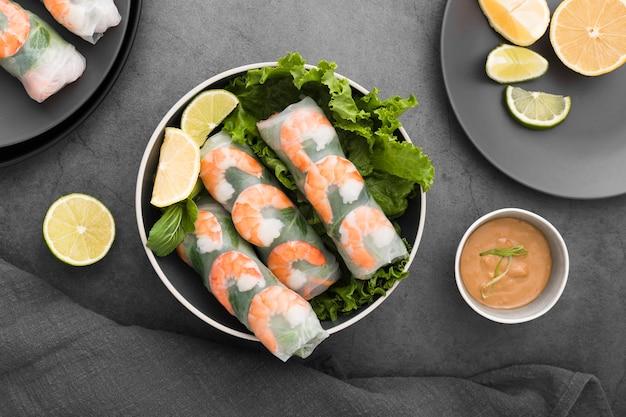 Ciotola di involtini di gamberi con insalata e limone Foto Gratuite