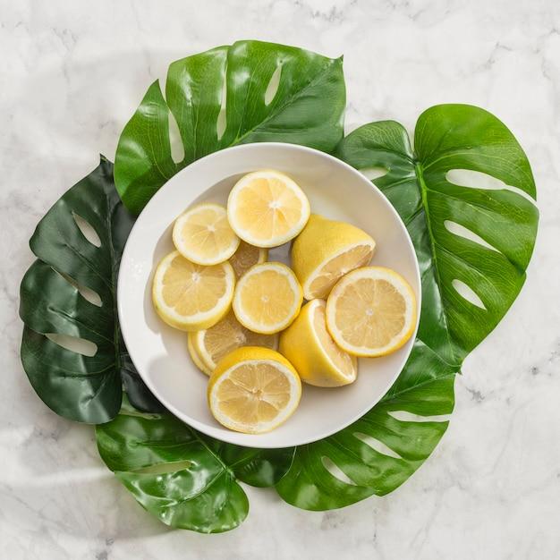Ciotola di limoni a fette con foglie di monstera Foto Gratuite