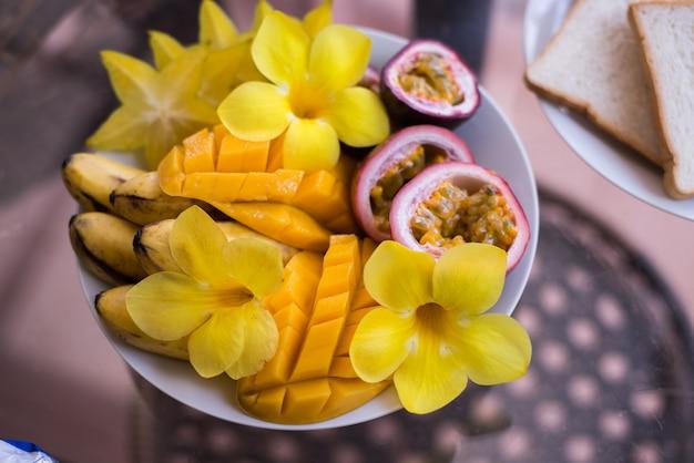 Ciotola di mango, banana, frutto della passione condita con fiori e frutta fresca Foto Premium