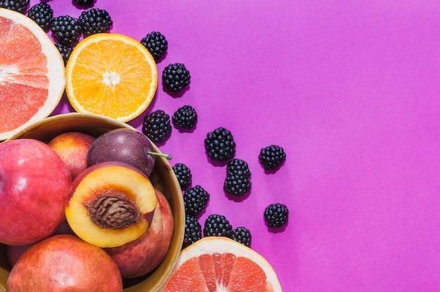 Ciotola di mela; pesca; arancia; uva frutta fette e more su sfondo viola Foto Gratuite