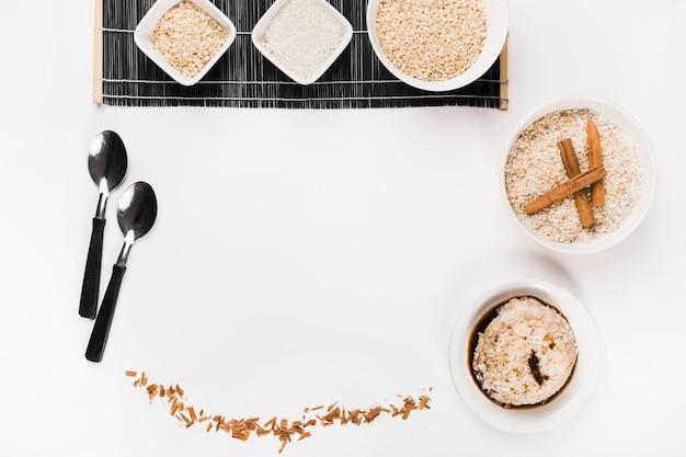 Ciotola di riso cruda con il cucchiaio e riso della salsa di soia su fondo bianco Foto Gratuite