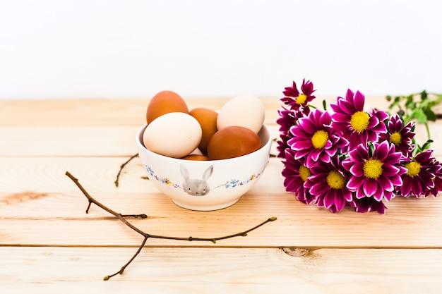 Ciotola di uova in ceramica, piatto di fondo in legno, preparazione per pasqua, prodotti agricoli, pollo e uova, decorazione della casa per le vacanze, rami degli alberi con gemme, primavera, bellissimo rosso brillante Foto Premium