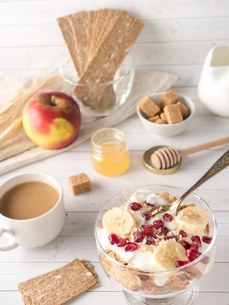 Ciotola di vetro con muesli e yogurt con banana, semi di melograno. Foto Premium