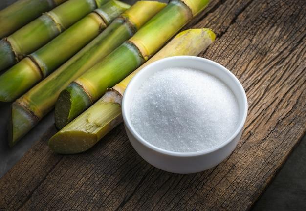 Ciotola di zucchero bianco con la canna da zucchero sulla tavola di legno. Foto Premium
