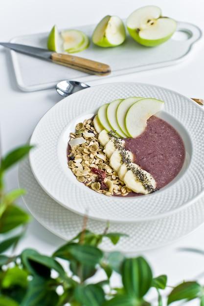 Ciotola frullato con banana, mela, semi di chia, farina d'avena e yogurt. Foto Premium