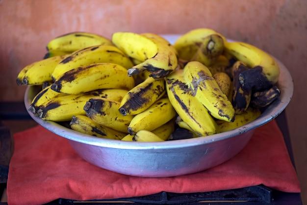 Ciotola in alluminio con un mucchio di banane molto mature Foto Premium