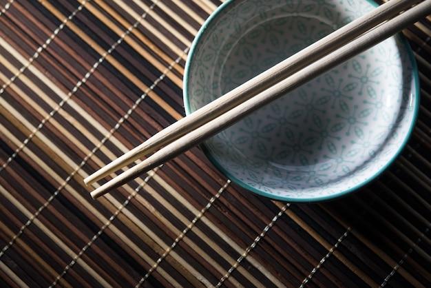 Ciotola in ceramica con le bacchette su sfondo di bambù Foto Premium