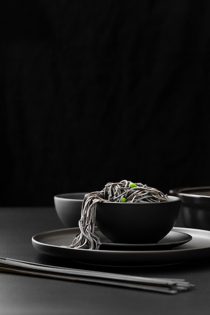 Ciotola nera con pasta su un piatto scuro Foto Gratuite