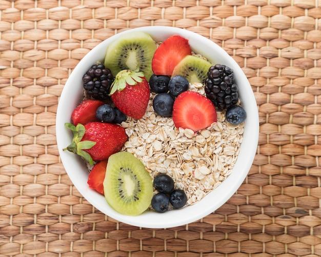 Ciotola ripiena di frutta e cereali piatto disteso Foto Gratuite