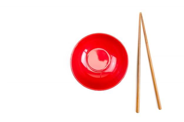 Ciotola rossa con le bacchette e isolata Foto Premium