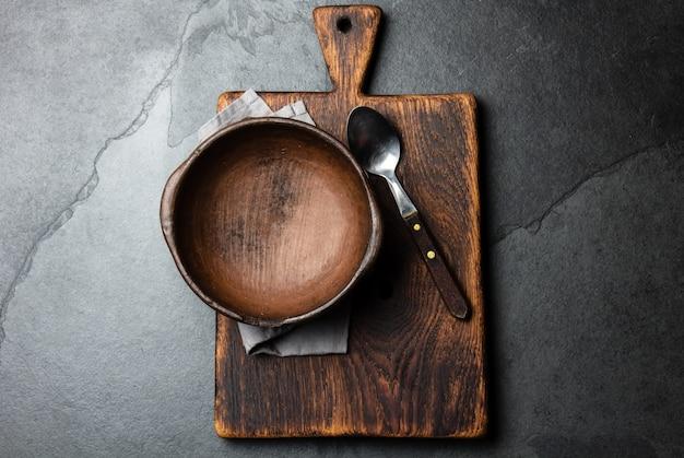Ciotola vuota d'argilla d'annata sui taglieri Foto Premium