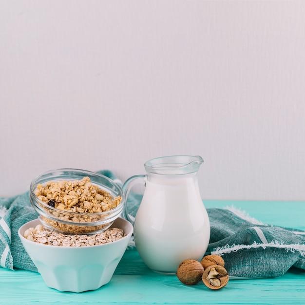 Ciotole di cereali; barattolo di latte e noci sul tavolo di legno Foto Gratuite
