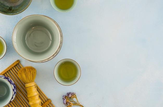 Ciotole di tè tradizionale e spazzola del tè sul contesto bianco Foto Gratuite