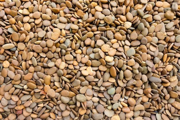 Ciottolo pietra o ciottoli pietra naturale marrone con texture di sfondo Foto Premium