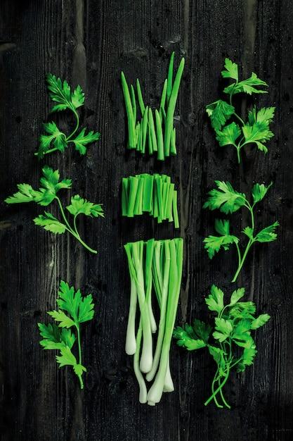 Cipolla e prezzemolo verdi freschi di taglio sullo scrittorio nero Foto Premium