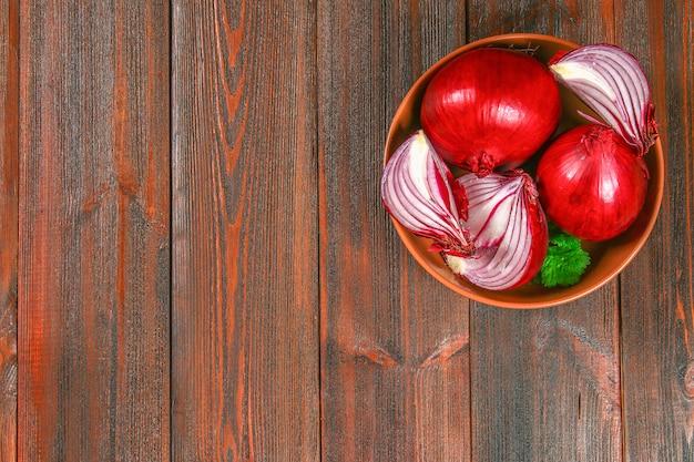 Cipolle rosse fresche e fette tritate su un tavolo di legno. vista dall'alto. Foto Premium