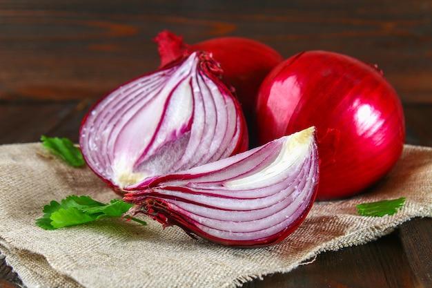 Cipolle rosse fresche e fette tritate su un tavolo di legno. Foto Premium