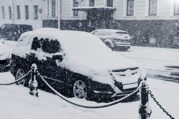 Città paralizzata durante forti nevicate. auto coperte di neve. ciclone potente durante l'inverno Foto Premium