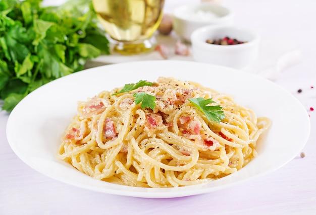 Classica pasta alla carbonara fatta in casa con pancetta, uova, parmigiano stagionato e salsa di panna. Foto Premium