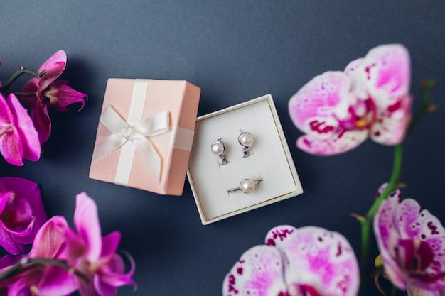 Classici gioielli alla moda retrò. orecchini ad anello in argento con perle in confezione regalo con orchidea viola. accessori alla moda Foto Premium