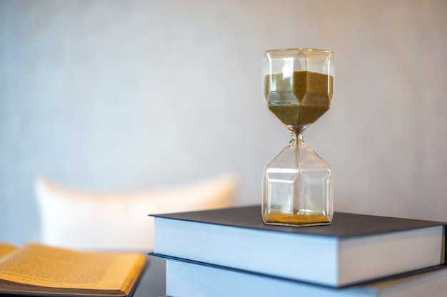 Clessidra e vecchio libro con sfondo sfocato. lascia lo spazio per copiare il testo. Foto Premium