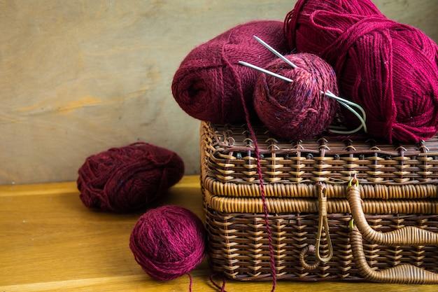 Clews di capsule di cesto di vimini d'epoca di filato di lana rosso, aghi sul tavolo di legno Foto Premium