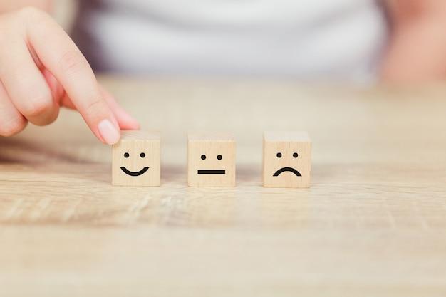 Cliente che preme emoticon del fronte di smiley sul cubo di legno Foto Premium