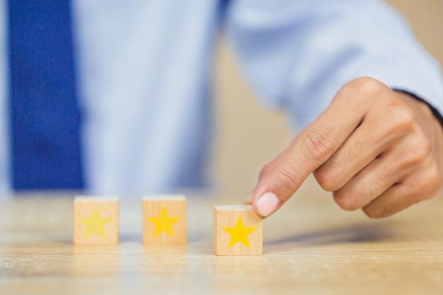 Cliente che preme stella sul cubo di legno Foto Premium