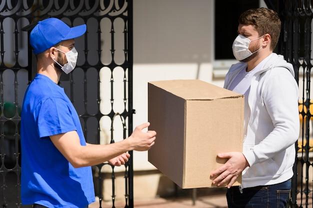 Cliente con maschera facciale che riceve pacchi dal fattorino Foto Gratuite