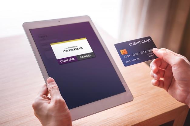 Cliente della giovane donna che usando la carta di credito e la compressa al pagamento online Foto Premium