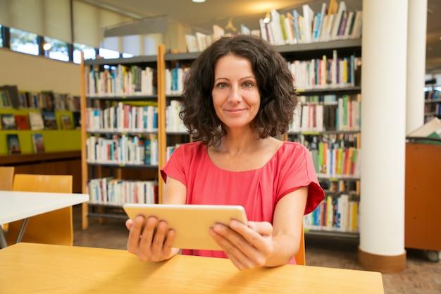 Cliente femminile soddisfatto con l'aggeggio che posa nella biblioteca pubblica Foto Gratuite