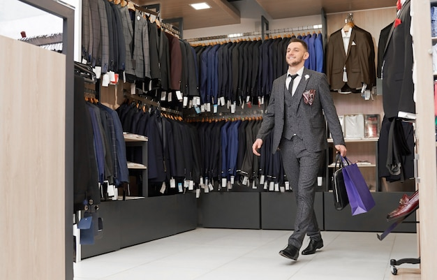 Cliente in abito in boutique con borse della spesa. Foto Gratuite