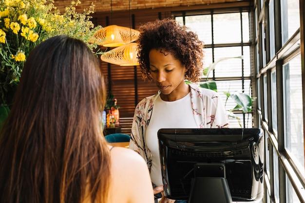 Cliente in piedi davanti al cassiere femminile nel ristorante Foto Gratuite