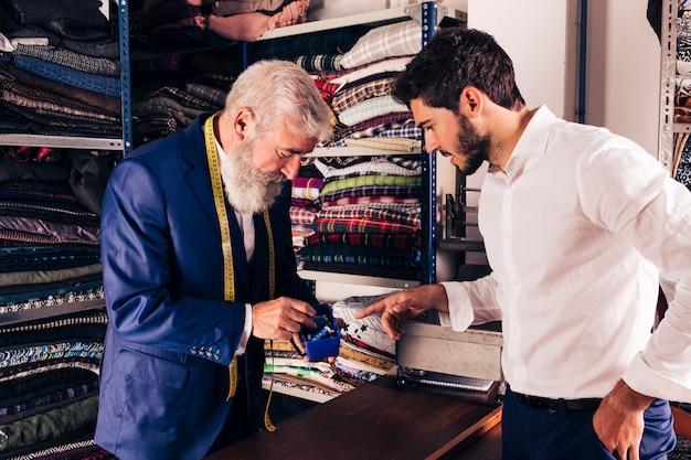 Cliente maschio che seleziona la bobina del filo con lo stilista maschio nel suo negozio Foto Gratuite