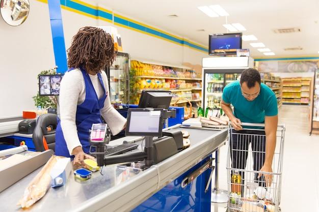 Cliente maschio nel mettere casual prodotti dal carrello al bancone Foto Gratuite