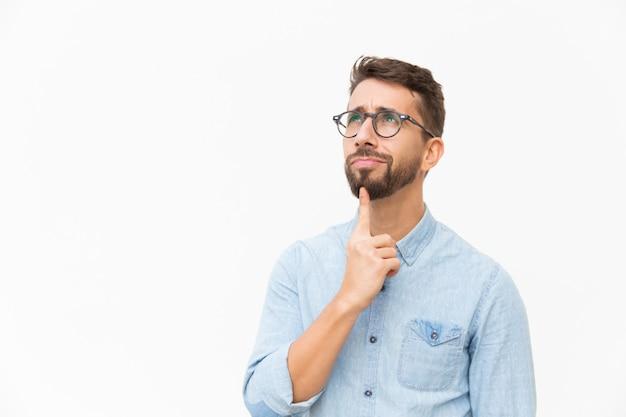 Cliente maschio pensieroso positivo che studia offerta speciale Foto Gratuite