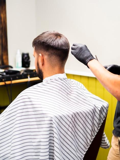 Cliente seduto su una sedia nel negozio di barbiere Foto Gratuite