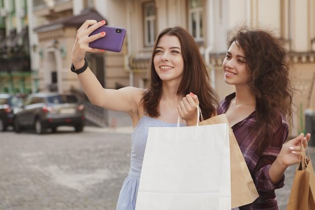 Clienti femminili allegri che per mezzo dello smart phone, scattare foto dopo lo shopping Foto Premium