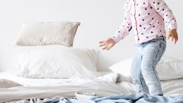 Close-up bambino in piedi nel letto Foto Gratuite