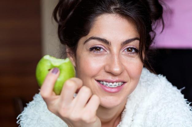 Close-up della donna allegra mangiando una mela Foto Gratuite