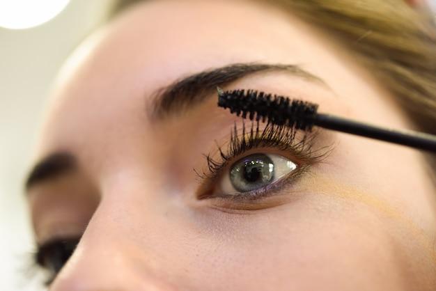 Close-up della donna di applicare il mascara per ciglia Foto Gratuite