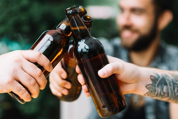 Close-up di amici tintinnano le bottiglie di birra all'aperto Foto Gratuite