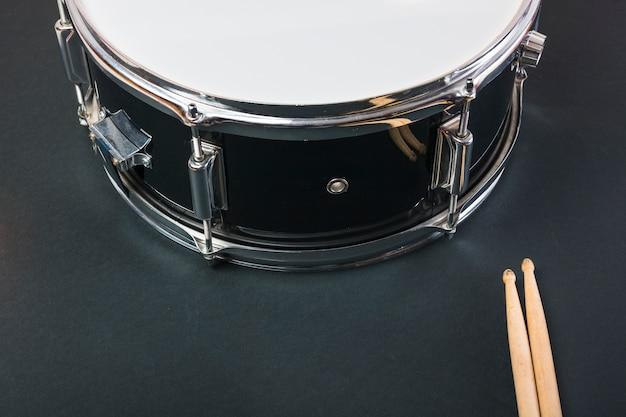 Close-up di bacchette di legno e tamburo su sfondo nero Foto Gratuite