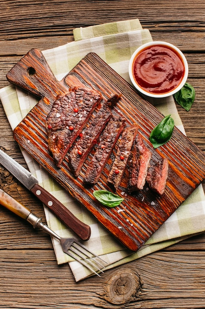 Close-up di bistecca fritta con salsa sul tavolo di legno Foto Gratuite