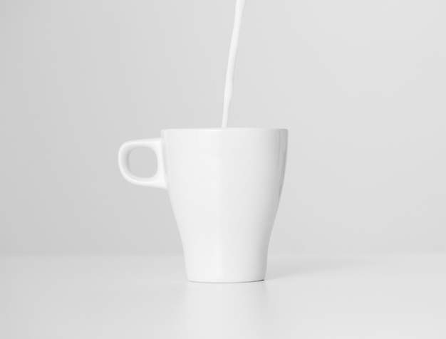 Close-up di latte versando nella tazza di ceramica Foto Gratuite