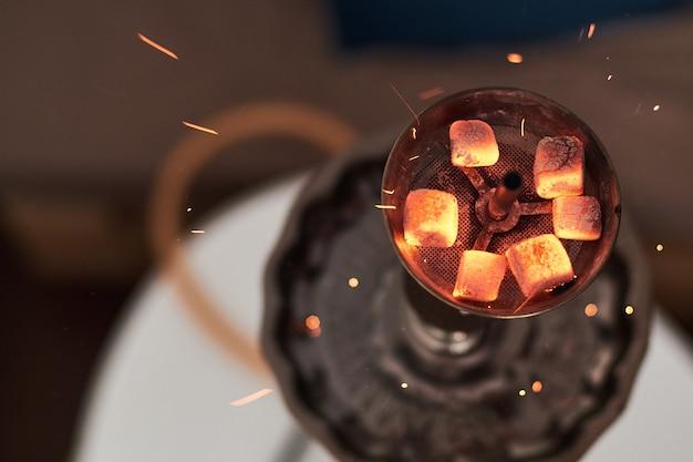 Close-up di narghilè shisha con carboni ardenti. scintille da respirare. narghilè moderno con carbone di cocco e fumo di narghilè. Foto Premium