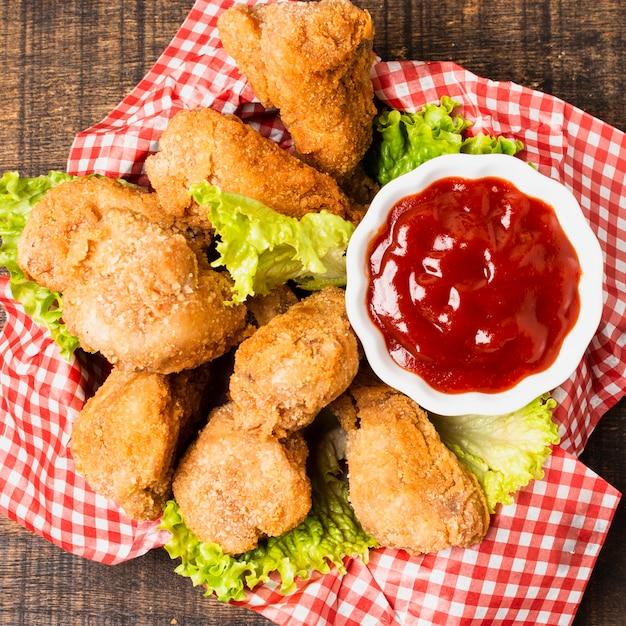 Close-up di pollo fritto con ketchup Foto Gratuite